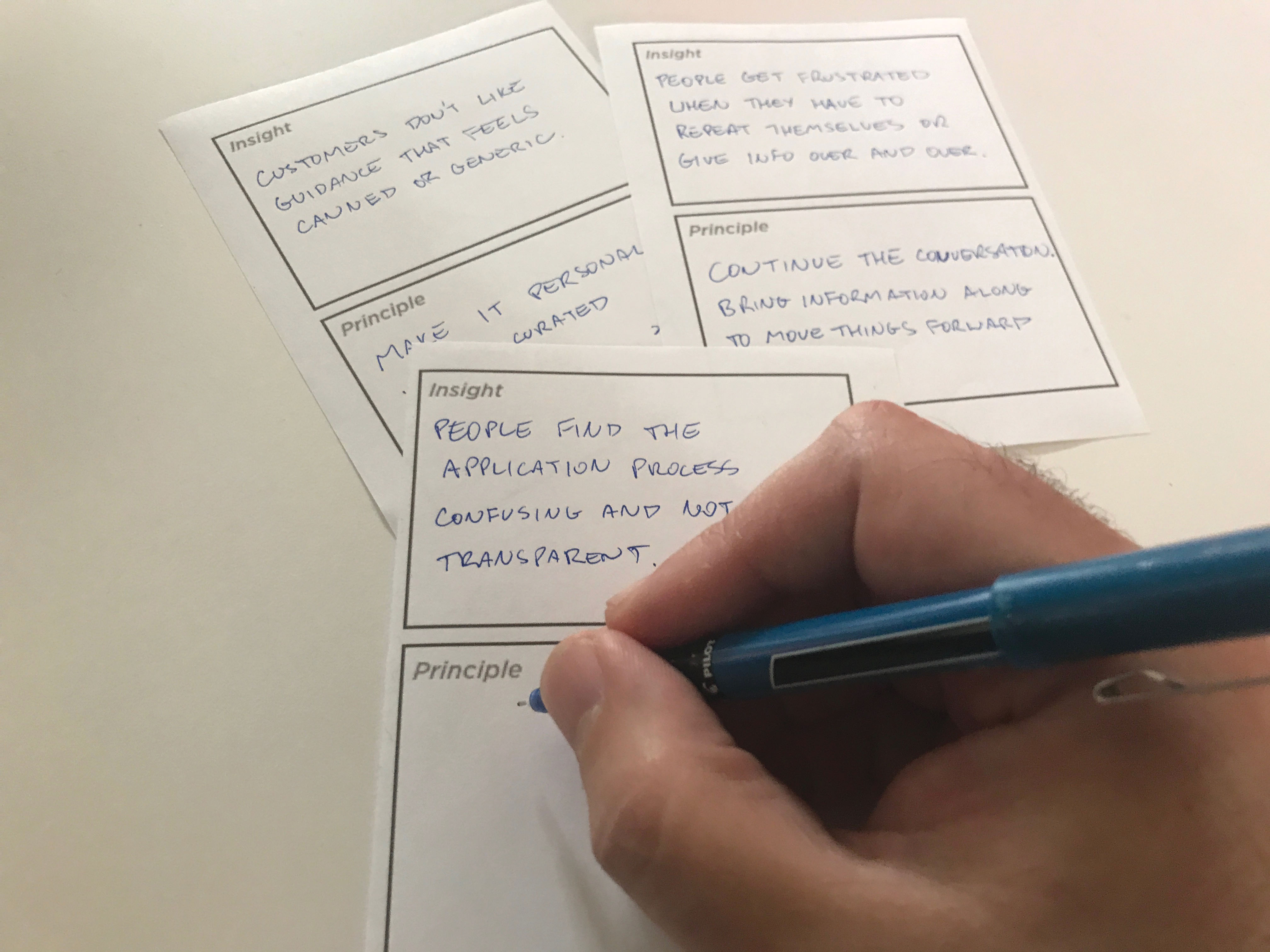 A hand with a pen writes notes with insights and corresponding principles