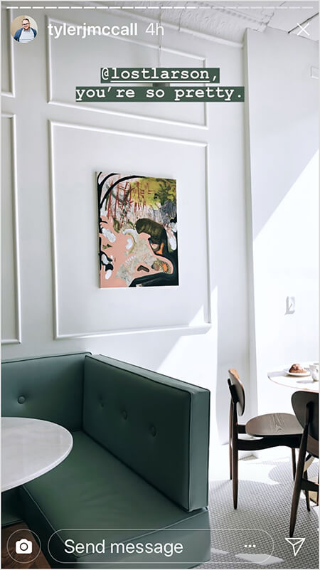 """Tyler J. McCall posts a photo in the middle his day-in-the-life story arc. The photo shows the interior of Lost Larson, with a green couch, a white marble-topped table, a white tile floor, and pale walls with art hung inside a square of white wood trim on a pale gray wall. Text on the post says """"@lostlarson, you're so pretty"""" as a reminder that his story includes a trip to Lost Larson."""