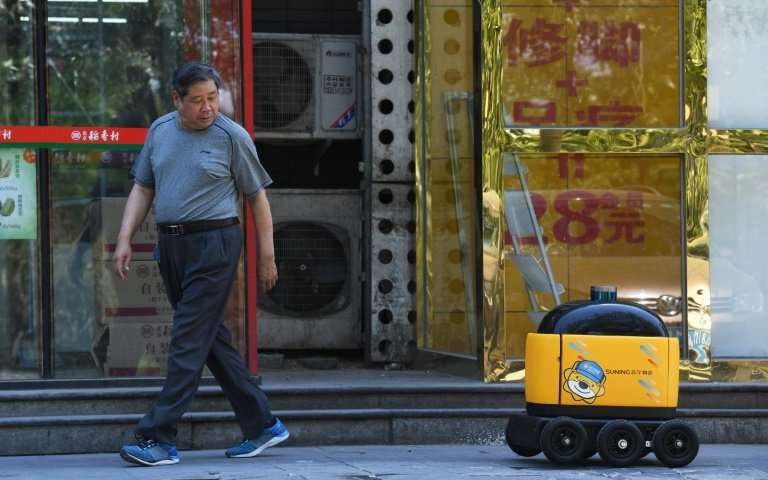 A delivery robot makes its way back to a supermarket after making a delivery during a demonstration in Beijing