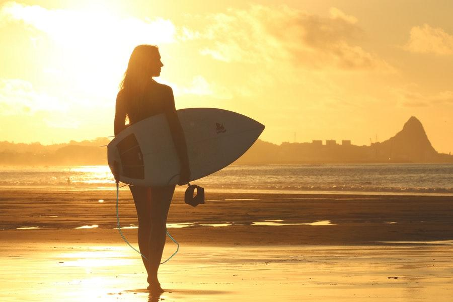 Woman with surfboard standing by sea shore