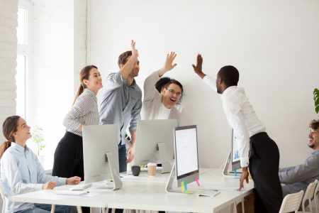 A team of happy customer service employees exchanging high fives.