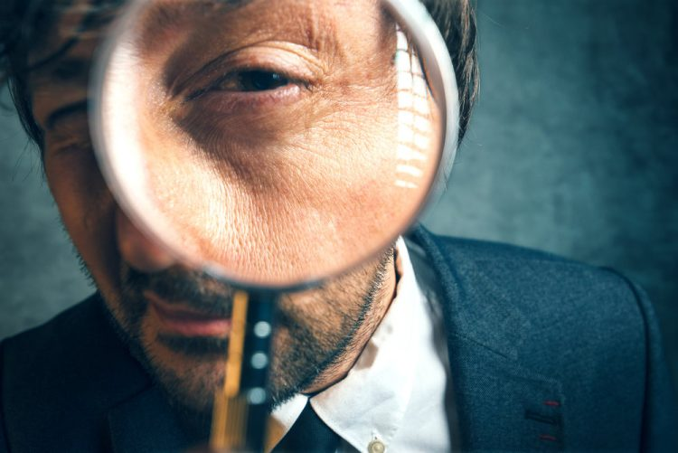 Close-up of a man looking through a magnifying glass.
