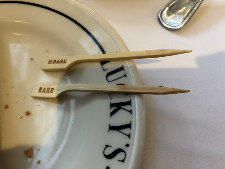 Two small wooden flags rest on a plate, one says