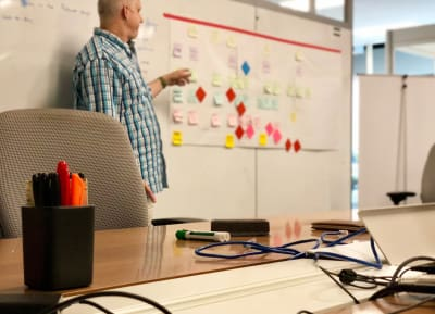 Prospective designer discussing their process through a whiteboard exercise during an interview.