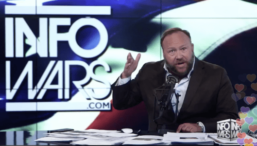 Alex Jones gestures with his hands at his broadcast desk.