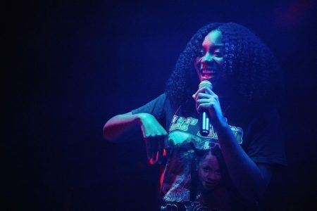 Noname stands with a mic in hand, lit by dramatic blue and red stage lighting