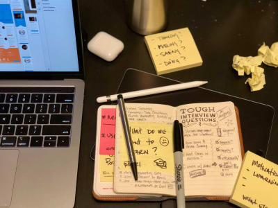 Notes taken during a designer interview shown along with Post-its, writing utensils, and a computer showing mock-ups.