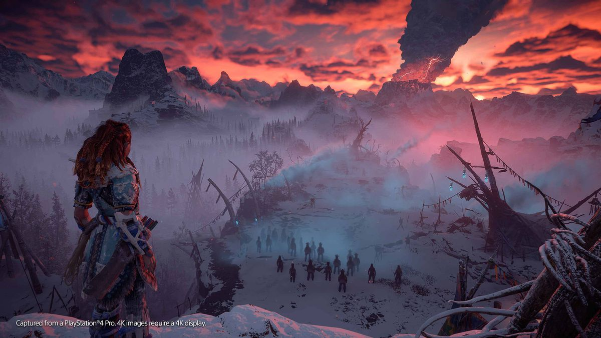 Horizon Zero Dawn: The Frozen Wilds - Aloy looks out over a snowy landscape toward a volcano