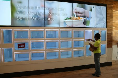 A customer picks up her food from a cubby at Eatsa, a largely automated restaurant in San Francisco.
