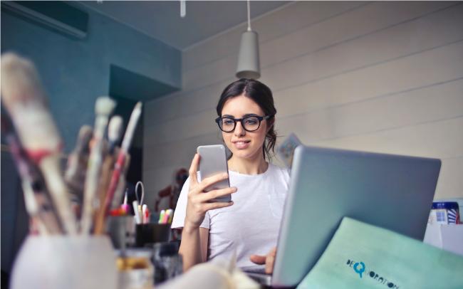 woman looking at phone sitting at art desk